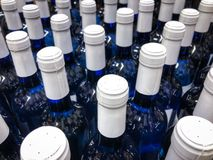 Wine bottles - many blue bottles with white label / bottlenecks stock photography