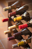 Wine bottles in rack. Red and white wine bottles stacked on wooden racks shot with limited depth of field Royalty Free Stock Image
