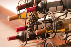 Wine bottles in rack. Red and white wine bottles stacked on iron rack shot with limited depth of field Royalty Free Stock Photography