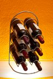 Wine bottles in rack. A collection of wine bottles stored in a wire rack on orange background Royalty Free Stock Photography