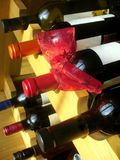 Wine bottles with red ribbon stacked on wooden rac Royalty Free Stock Photos