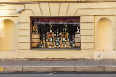 Wine bottles in the restaurant`s window. St. Petersburg, Russia - May 01, 2019: An assortment of wine bottles in a restaurant window.  ancient wall and window of royalty free stock photography