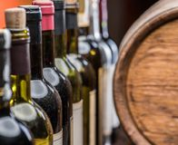 Wine bottles in row and oak wine keg. Stock Images