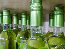 Wine bottles stacked on wooden racks with limited depth of Stock Images