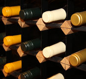 Wine bottles stacked on wooden racks. Shallow depth of field Royalty Free Stock Photo