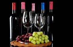 Wine bottles, wine glasses and grapes. On a wooden board isolated on a black background stock photography