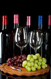 Wine bottles, wine glasses and grapes. On a wooden board isolated on a black background royalty free stock photo