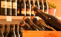 Wine bottles  in wine store. Wine bottles on wooden shelf in wine store Royalty Free Stock Photo
