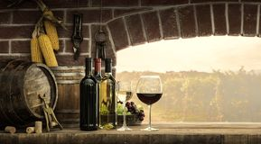 Cellar window and wine bottles. Wine bottles, wineglasses, barrels next to the cellar window and beautiful panoramic view of countryside vineyards: winemaking Royalty Free Stock Images