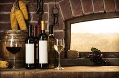 Cellar window and wine bottles. Wine bottles, wineglasses, barrels next to the cellar window and beautiful panoramic view of countryside vineyards: winemaking Stock Photos