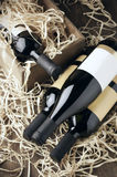 Wine bottles in wooden box and straw Royalty Free Stock Images