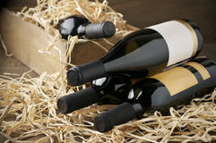 Wine bottles in wooden box and straw Royalty Free Stock Image