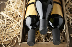 Wine bottles in wooden box and straw Royalty Free Stock Photography