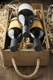 Wine bottles in wooden box and straw Royalty Free Stock Photos