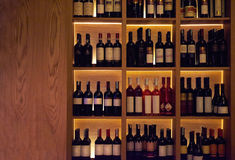 Wine bottles on a wooden shelf. Stock Images