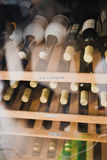 Wine bottles. On wooden shelf in wine store Stock Image