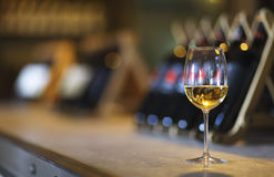 Wine bottles on a wooden shelf. Wine bar. Close up on glass of white wine Stock Images