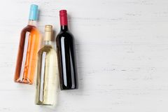 Wine bottles. On wooden table. Red, rose and white wine. Top view with space for your text stock photos