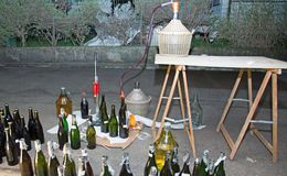Wine bottling in the backyard with the Carboy and glass bottles Royalty Free Stock Photography