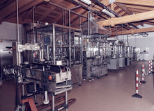 Wine bottling equipment line in a hangar, toned Royalty Free Stock Photos
