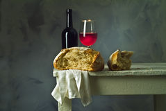Wine and bread. Red wine glass, bottle and loaf of sour dough bread Stock Images