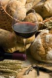 Wine and Bread 5. An inviting glass of red wine along with an assortment of fresh breads Royalty Free Stock Image