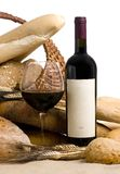 Wine with bread blank label. A glass of wine and assorted breads. The wine bottle has a blank lable that can be filled in Stock Image