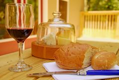 Wine, Bread and Cheese. Attractive spread of wine, bread, and cheese under dome on back deck in afternoon sun Stock Image