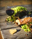 Wine, bread, letuce and cheese on the wooden table Stock Photography