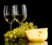 Wine, a bunch of white grapes and a piece of cheese. Two glasses of white wine, a bunch of white grapes and cheese on black background Royalty Free Stock Image