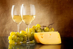Wine, a bunch of white grapes and a piece of cheese. Two glasses of white wine, a bunch of white grapes and cheese on linen background Stock Photos