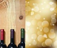 Wine buteljerar på ett trä bordlägger, och abstrakt begrepp tänder på guld- champagne Arkivbilder