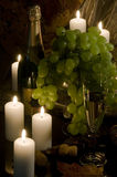 Wine of a candle and grapes. Champagne, glass with wine and candles on a table against from a stopper and a fabric royalty free stock photography