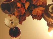 Wine, Candle and Roses. Close-up of a glass of wine under a soft light, in companion of a dried roses bouquet, and a candle. all these romantic elements royalty free stock photography