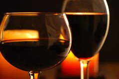 Wine and candles #2. Two glasses of win set against candle light Royalty Free Stock Photography