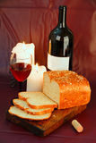 Wine, candles and bread. Glass of red wine with dark colored bottle, lit candles and partially sliced loaf of bread on wooden board against burgundy background Stock Photography