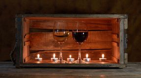 Wine and candles. Five candles ans two wine glasses in a wooden box royalty free stock photography