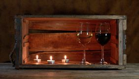 Wine and candles. Three candles ans two wine glasses in a wooden box Royalty Free Stock Photography