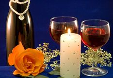 Wine candlight and rose. A closeup view of two glasses filled with red wine, a white candle and a peach rose with a bottle of wine and baby's breath in the Stock Photo
