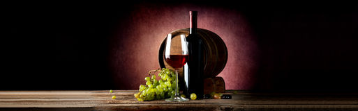 Wine and cask on table. Wine and wooden cask on table and vinous background stock image