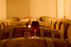 Wine Cellar. Wine glass with red wine on a cask in wine cellar Stock Photos