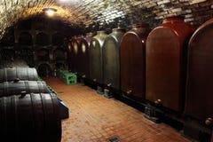 Wine cellar. Old generic wine cellar - wooden barrels, huge ceramic containers and racks of bottles. Vintage wines Stock Image