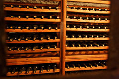 Wine Cellar. A wood wine cellar with many bottles in an orange moody light Stock Photo