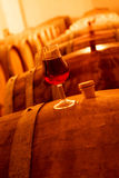 Wine Cellar. Wine glass with red wine on a cask in wine cellar Stock Photo