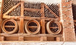 Wine cellar in bar, winery or hotel, with glass bottles stuck in rustic wooden shelves of rural storage. Wine cellar in bar, winery or hotel, with glass bottles royalty free stock photo