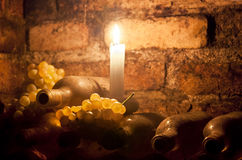 Wine cellar in candlelight. Bottles of wine and bunches of grapes lit by candlelight in a wine cellar Royalty Free Stock Photo
