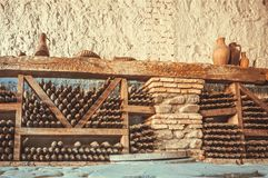 Wine cellar with many dusty glass bottles and rustic wooden shelves on stone walls of rural storage of winery. Wine cellar with many glass bottles and rustic royalty free stock photo