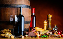 Wine cellar. One glass of red wine and two bottles of rose and red wine in a rustic cellar with food royalty free stock photos