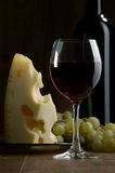 Wine and cheese. Glass of wine and cheese on a dark background Stock Photo