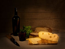 Wine and cheese. The still-life is made of cheese, bread, wine and spinach Stock Photos